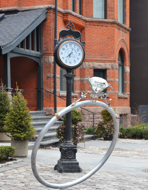 a very large fake diamond ring, single stone, sculpture size, about 3 feet in diameter, stands in front of an old fashioned clock in front of some stores