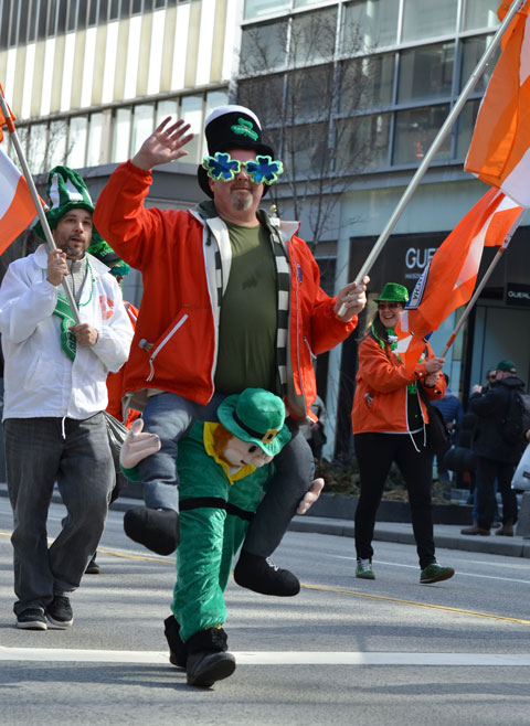 st. patricks day parade, man wearing a costume that makes it look like a large leprechaun is grabbing him around the knees