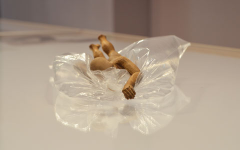 a little wooden human figure is doing the front crawl, one arm outstretched, on a bubble of clear plastic on a table top