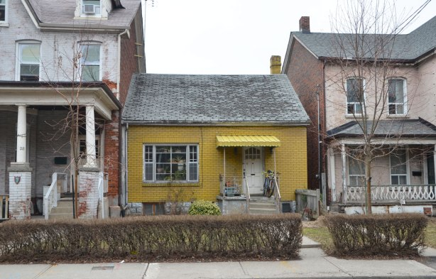 a small yellow bungalow is between two largeer and taller houses. It has a hedge in front and a yellow awning over the front door.