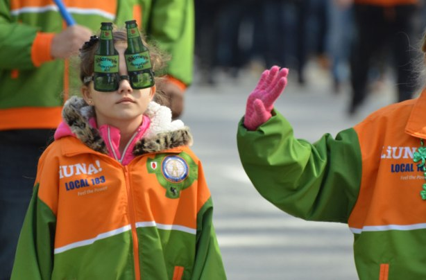 a young girl with a liuna union jacket on walks in a parade. she is wearing beer bottle shaped glasses