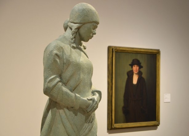 a sculpture of a woman with a child on her back, called Eskimo Mother and child by Frances Loring. She stands by a painting by Lawren Harris called Bess which a portrait of a woman in a black hat and black coat
