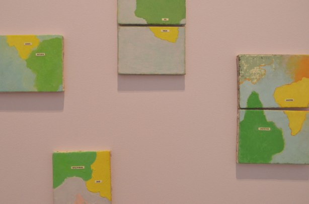 4 small green and yellow pictures on a pink wall