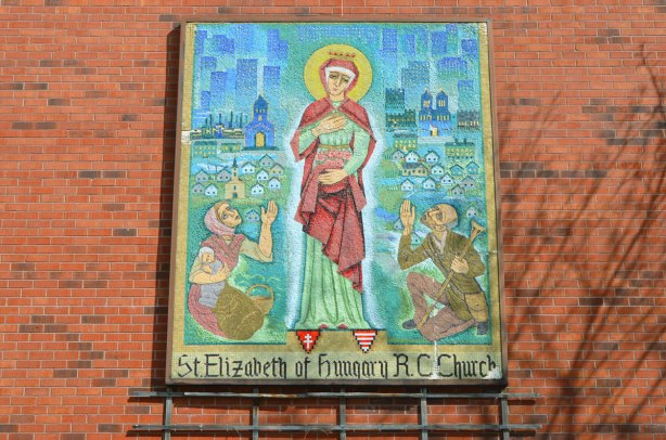 mosaic on the exterior brick wall of St. Elizabeth of Hungary RC Church showing St. Elizabeth and two people kneeling beside her.