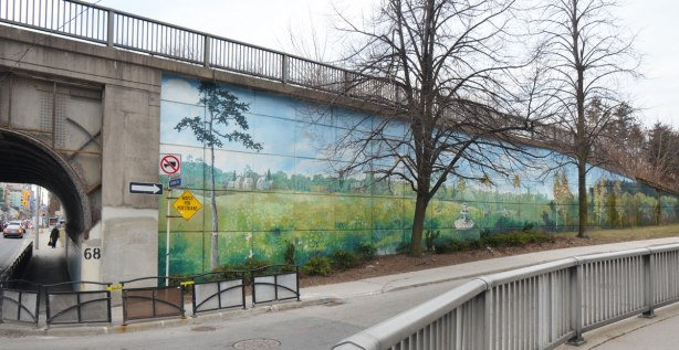 mural painted along the side of a wall that is part of the embankment for a railway bridge Mural is a country scene, grass and fields, a farm in the distance and a couple of trees.