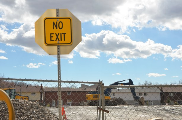 a construction site where the houses on a a whole street have been demolished. The no exit sign for the street still remains., the site is behind a chainlink fence