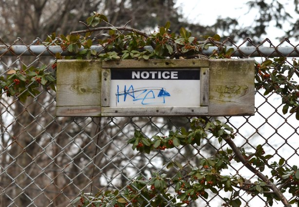 a sign on a chainlink fence that says notice. otherwise it is blank