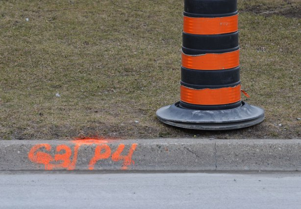 black and orange construction cone site beside a kerb on which numbers have been spray painted in orange