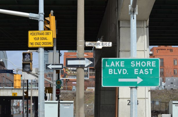 traffic signs at an intersection, at Lakeshore Blvd East, two one way signs pointing in the opposite directions, an elevated expressway also in the picture