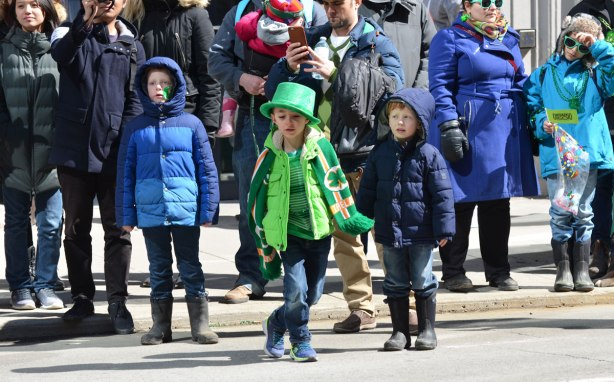 three boys among a crowd of onlookers at a parade. The boy in the middle is wearing green and dancing as he watches