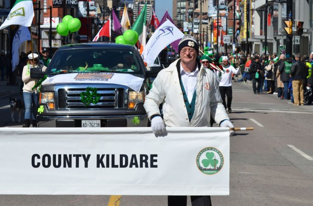 a man holds one end of a white banner that says County Kildare, St. Patricks Day parade