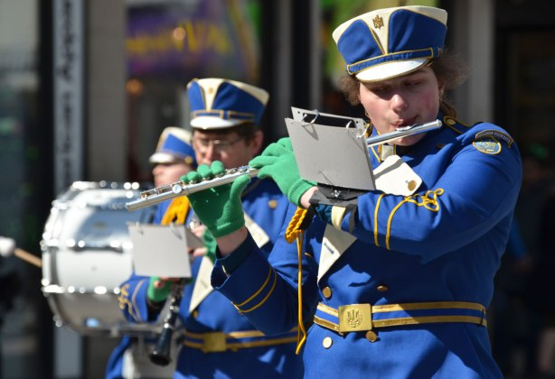 a flute player in a blue uniform plays and walks in a parade. Other musicians in the background