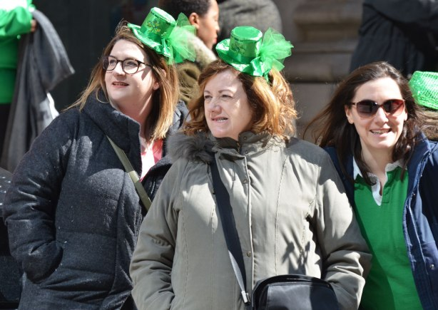 two women with little green hats perched on their heads watch the St. Patricks Day parade