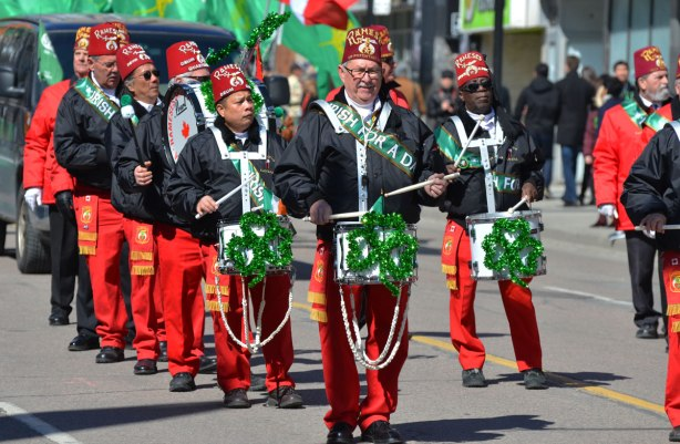 Ramses shriners band marches and plays in the St. Patrick Day parade. Red trousers, black jackets, large green shamrocks decorating their drums