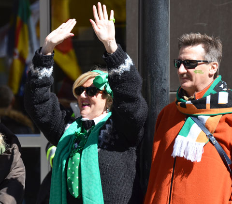 a woman cheers as she watches a parade from the sidewalk. Her partner is standing beside her