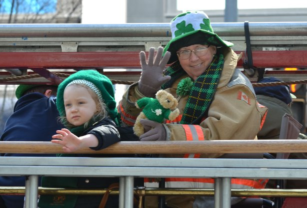 a middle aged woman in a fireman's jacket sits on a float in a parade (firetruck?) whe is holding a small teddy bear with a green sweater and a young girl is with her