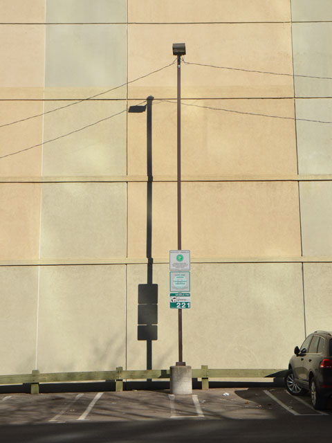 sun shining on a wall, one post with a sign on it is in the picture, along with its shadow