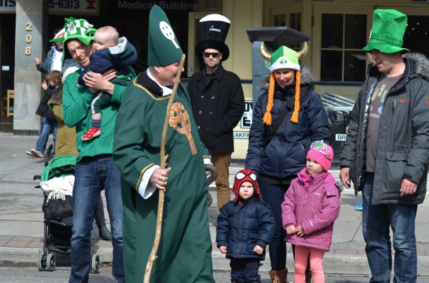 St. Patrick in the parade, talking to spectators on the sidewalk