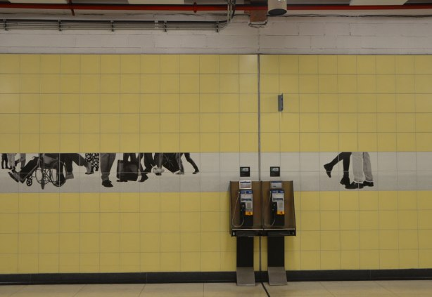 photos of peoples legs and feet in black and white on tiles on a yellow tiled subway station wall, over and beside two Bell pay phones, artwork by Sylvie Belanger