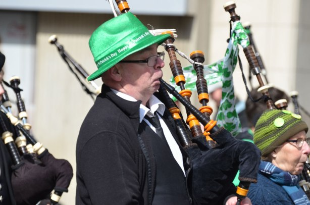 bagpipe player wearing a green hat for St. Patricks day