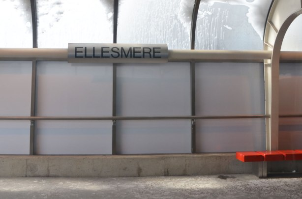 interior wall of Ellesmere station, covered (plastic?) glass wall, large black letters saying Ellesmere, and a bright red bench, snow on the curved translucent roof