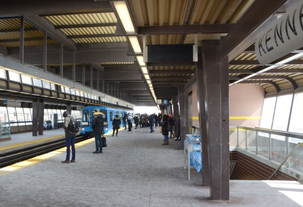 platform at Kennedy SRT station with people waiting as a blue train arrives