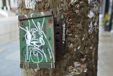 a green piece of metal attached to a wood hydro pole with a white drawing of a poser bunny on it.   The word honest in white letters is written beside the bunny