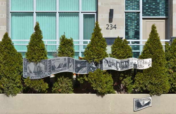 public art in front of a condo building that is a ribbon made of metal, flat, etched with a series of vintage Canadian postage stamps images