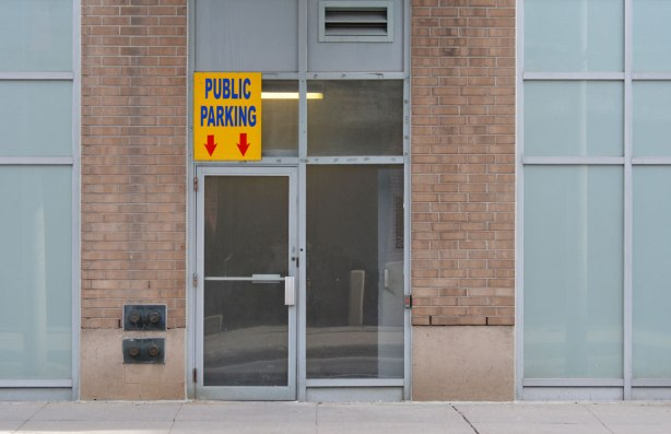 drab double glass doors on a drab light brown brick building with a sign that says public parking with arrows pointing to the door, The sign is above the door.
