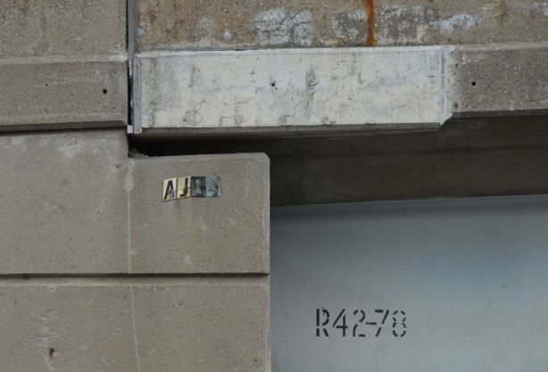 close up of the side of a concrete structure on a ramp of an expressway, there are two number sequences there. In stencil it says R42-78 and in stickers, AJ48