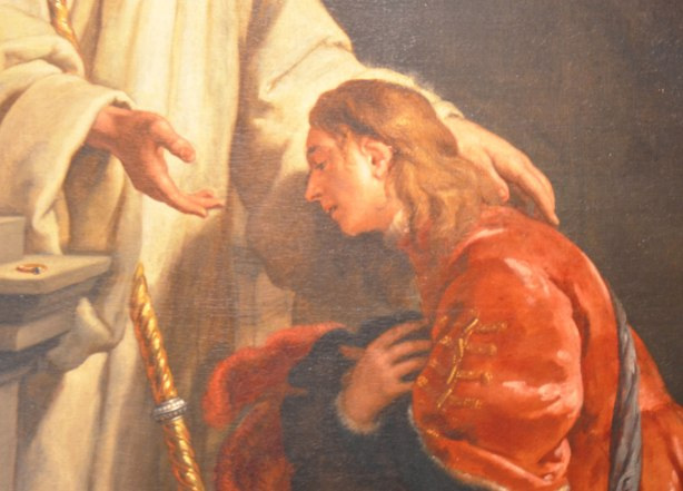 part of a religious painting of a young man in a red robe kneeling before another man in white who has one hand on the young man's shoulder.