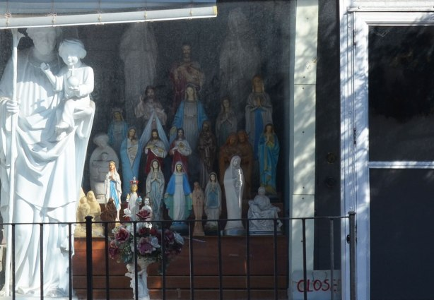 store window, selling statues of religios figures, many statues of Mary and Jesus.