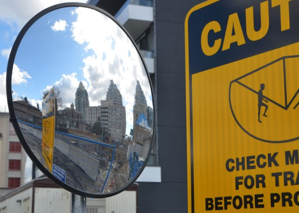a convex mirror beside a black and yellow caution sign, condos are reflected in the mirror