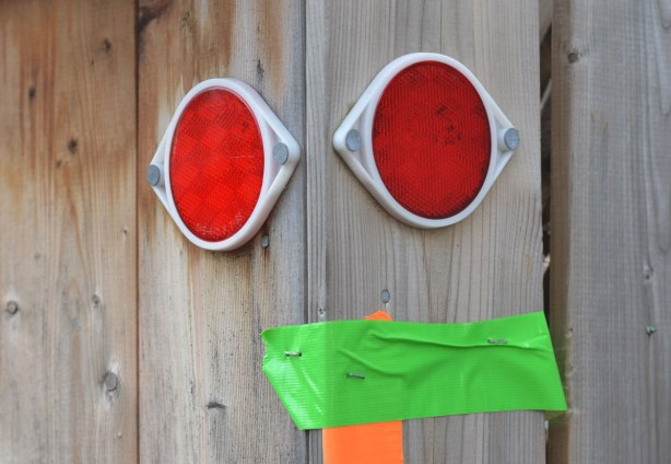 two round red reflectors mounted on a wood fence, look like two eyes, a piece of green tape is also on the fence in such a way that it looks like the mouth
