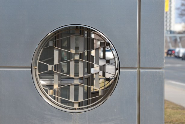 a round window with a metal grille inside. Grille is made of trapezoid shapes in a repeating pattern.