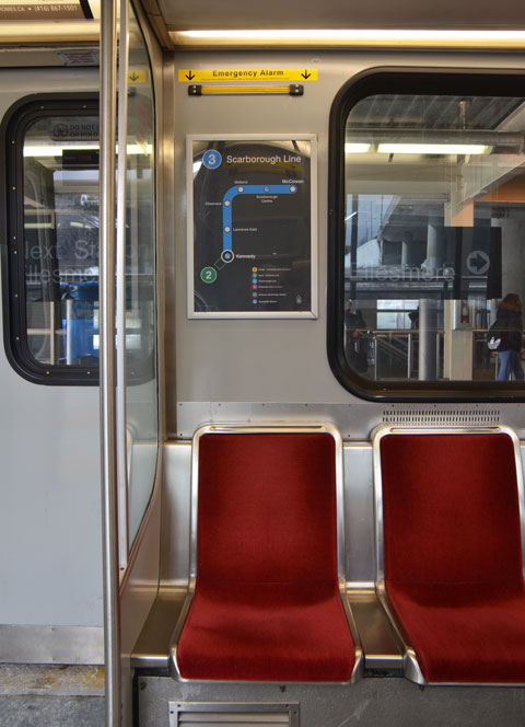 a map of the SRT route is on the wall behind two red seats of an SRT car, view out the window is not easy to see but it is the platform at Lawrence East station