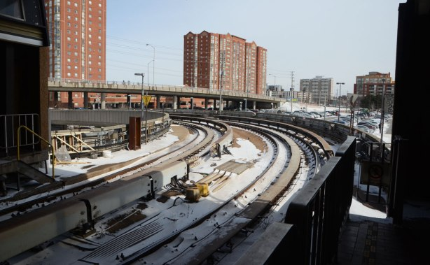 SRT tracks curve away from platform, outside, apartment building in the background, some snow on the tracks