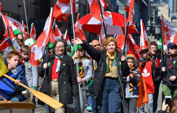 a group of adults and youth from Scouts Canada walk in the St. Patricks day parade, carrying lots of Canadian flags