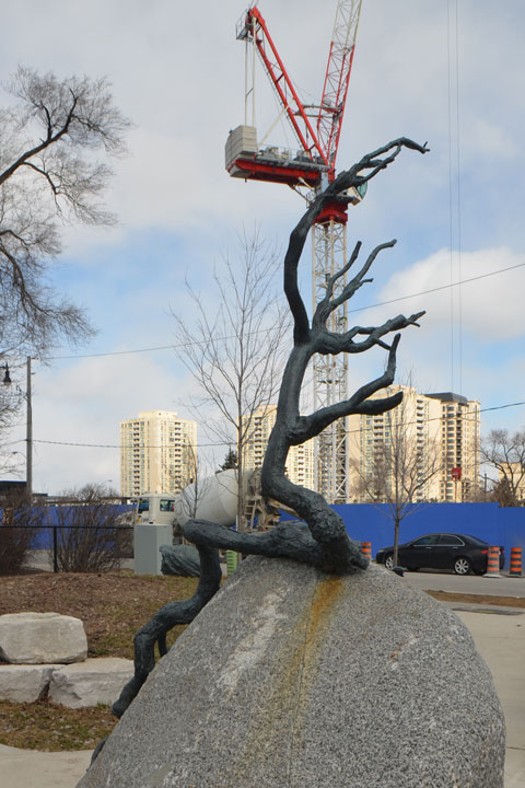 small sculpture in a park of a sapling on a rock with its roots growing over the surface of the rock - crane and construction site in the background