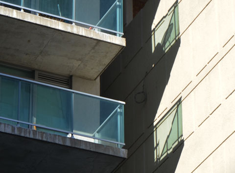 light reflecting from balconies along with shadows make phantom balconies on the building beside it