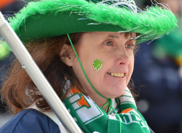 a woman in a green cowboy hat with a green fringe, a green shamrock sticker on her cheek and wearing a green, orange and white scarf