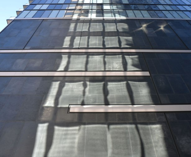 looking up a tall building that is black on the exterior and has light reflected from a glass building beside it.