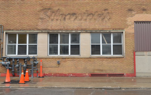 empty brick building, with ghost of sign that said Silversides in cursive writing,