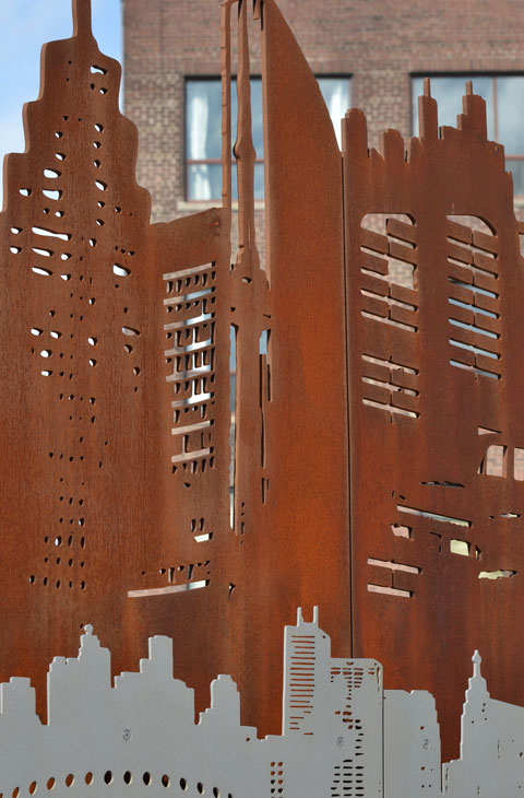 rusted metal cut out, part of a public art installation, cut outs look like houses, polished steel cutouts below the rusty ones.