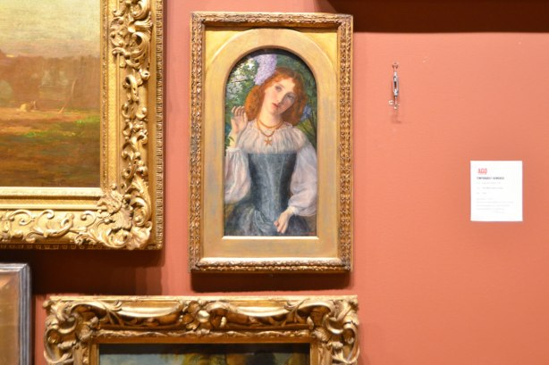 small painting of a red headed woman torso, amrs, and head, in a gold frame on a wall with lots of other paintings, except on e is missing and there is a white sign saying why its missing