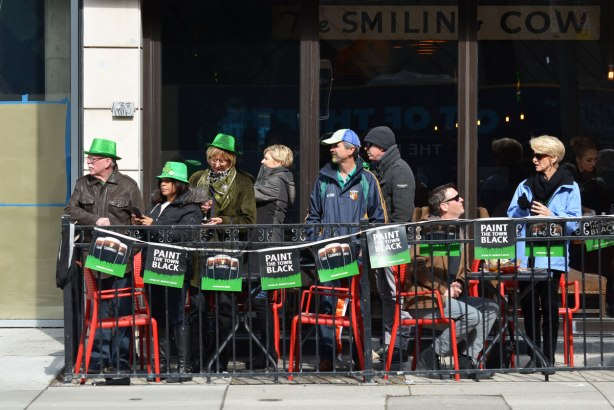 people standing and sitting on a small outdoor patio, on the sidewalk, watching the St. Patricks day parade go past. The bar is the Smiling Cow.