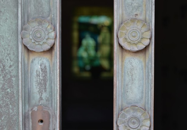 looking through the metal bars of a window, bars have little flower shaped metal pieces on it, looking into vault in cemetery, stained glas window in the background.