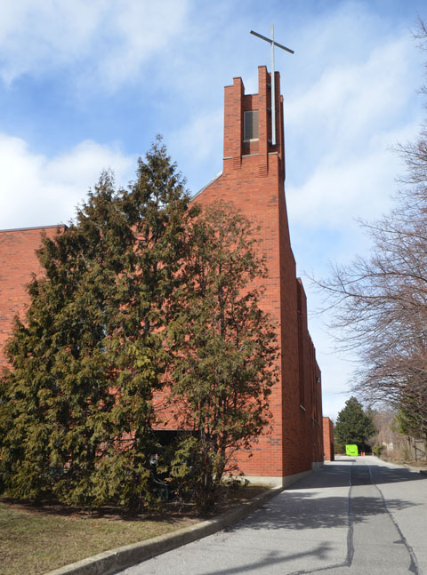 steeple of St. Elizabeth of HUngary RC church, modern brick building with simple cross on the top