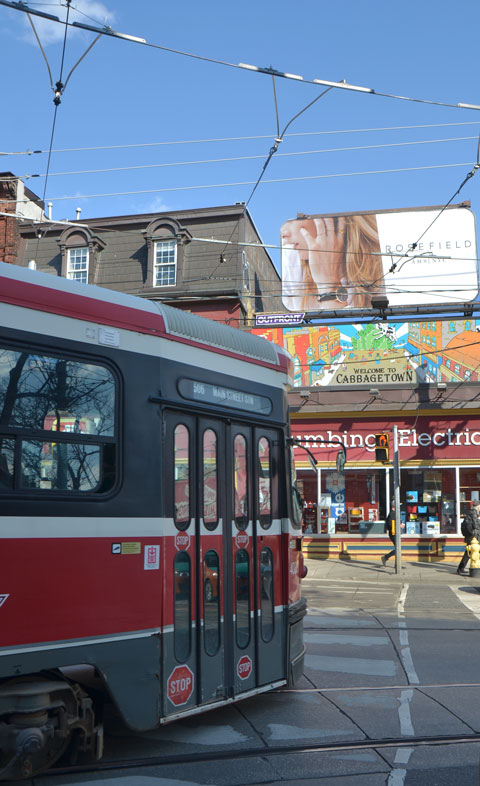 TTC streetcar, Carlton car, turns from Parliament street onto Carlton, stores, sidewalk and people in the background, reflections in street car windows.
