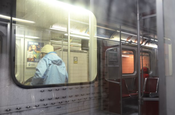 reflections of a woman in a red jacket sitting on the subway, reflected in the window beside a woman who is standing on the platform